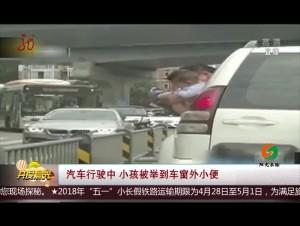 汽车行驶中 小孩被举到车窗外小便