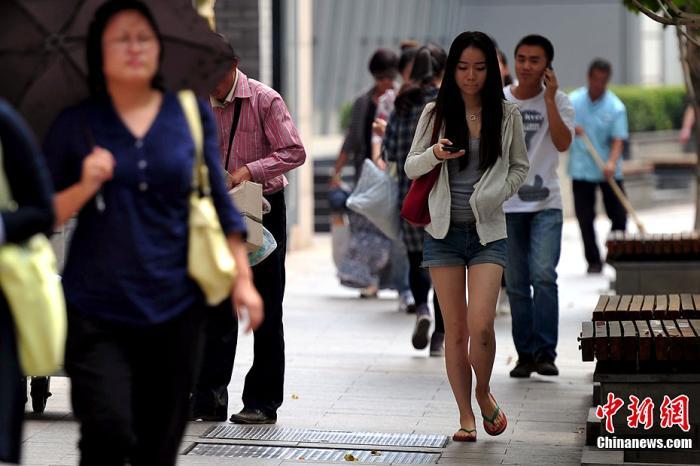 """白露PC配图。""""白露身不露"""" ,北京街头行人""""混搭装""""出行。<a target='_blank' href='http://www.chinanews.com/' >中新网</a>记者 金硕 摄"""