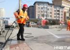 哈尔滨:环卫工人清洗街路设施 打造洁净城市环境