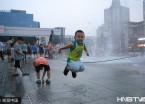 哈尔滨:35℃闷热天 儿童嬉戏喷泉边(组图)