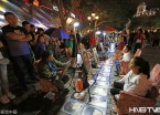 哈尔滨:中央大街画像生意人气旺 游客排长队体验