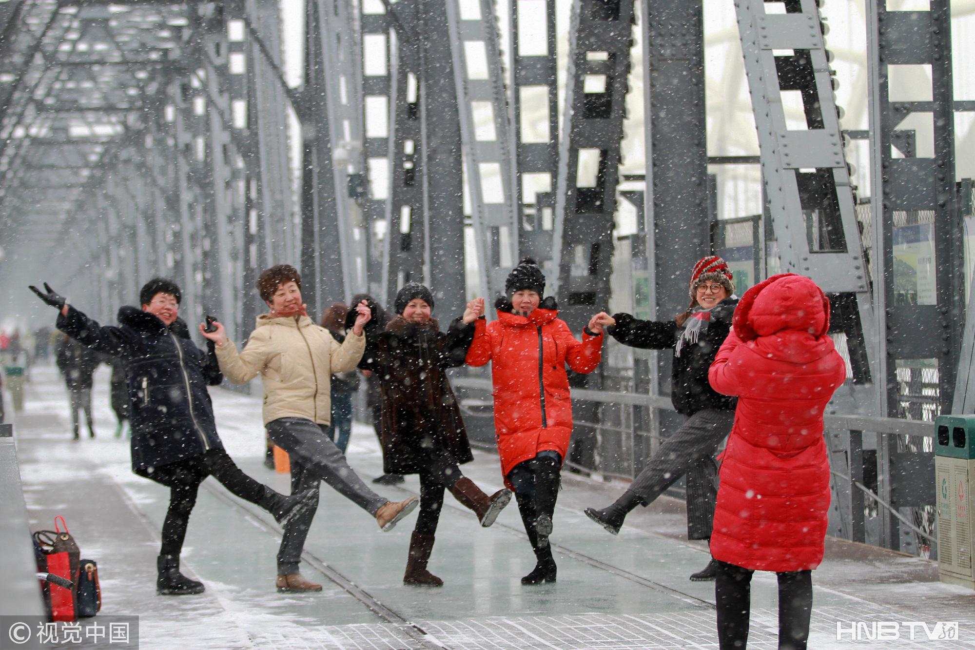 哈尔滨迎下雪天 游客扎堆与地标建筑合影(组图)