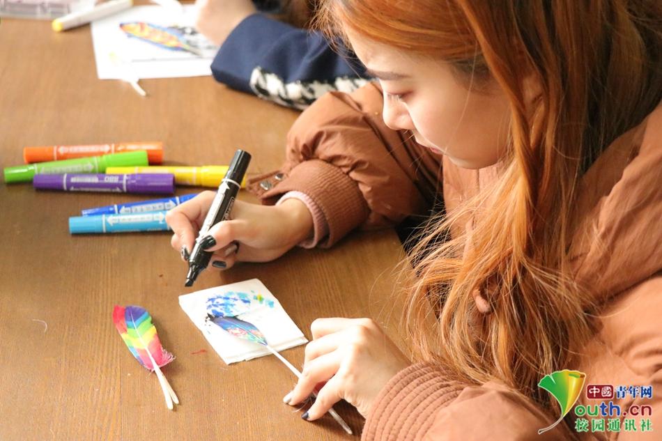 河南高校艺术生巧用专业特色 在羽毛上作画送同学