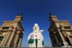 哈尔滨:超大雪人再穿新装 举牌引人拍照(组图)