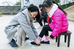 周迅致力公益担任爱心大使 蹲地为孩子穿鞋无架子