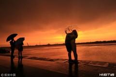 哈尔滨雨中霞光艳丽 引来众人撑伞观看(组图)
